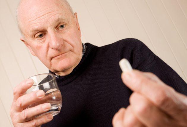 Пожилой мужчина принимает лекарство